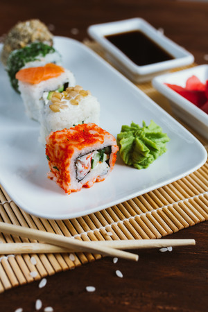 Sushi set on a dark wood background with wasabi, ginger and soy sauce Stock Photo