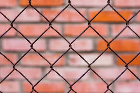 Fence of metal mesh against a brick wall, background