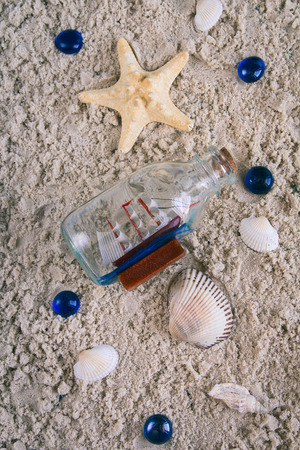 Wooden blue background in marine style. Starfish, sand, bottle with ship.