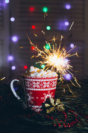 The Sparkler in a mug of cocoa with marshmallows. Selective focus. Christmas concept.