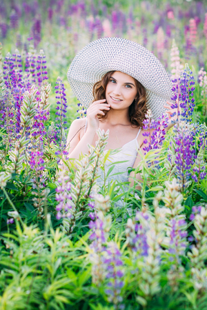 Beautiful young girl in a white dress and hat holding a bouquet of lupine at sunset on the field. The toning. The concept of nature and romance.