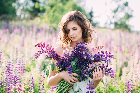 Beautiful young girl in a white dress holding a bouquet of lupine at sunset on the field. The toning.  The concept of nature and romance. Stock Photo