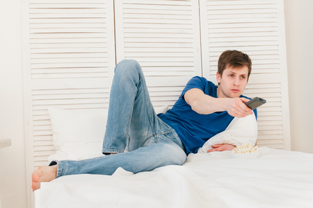dissatisfaction: Young handsome man watching TV sitting on the bed eating popcorn. Man is watching a movie.
