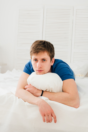 dissatisfaction: Man watching TV lying on the bed. A man is watching a movie. Stock Photo