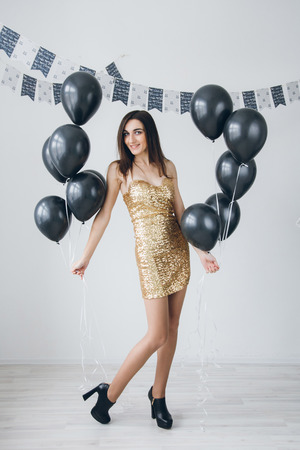 Young beautiful girl in a gold dress with black balloons. Toning.