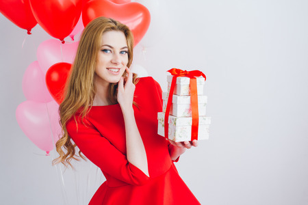 Beautiful girl in red dress with balloons in the shape of a heart holds boxes with gifts. The concept of love, Valentine's day. Toning. Stock Photo - 76917517
