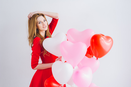 Beautiful girl in red dress with balloons in the shape of a heart. The concept of love, Valentines day. Toning.
