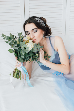 Boudoir brides morning. Young beautiful woman with a bouquet in a negligee preparing for their wedding day. Toning.