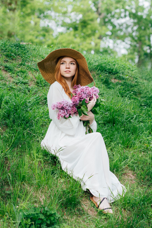 Beautiful redhead girl with a bouquet of lilacs in hand in a spring garden. Portrait. Toning.