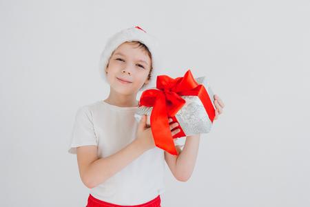 De jongen in de rode doos van de de holdingsgift van de Kerstmanhoed op witte achtergrond. Kerst concept.