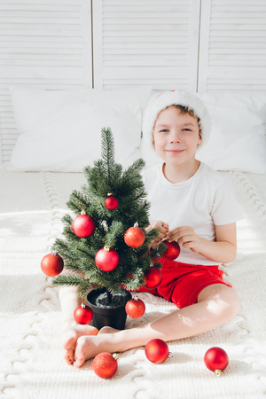 cute boy in red santa hat decorates a small christmas tree balls sitting on the bed - Small Christmas Tree Ornaments