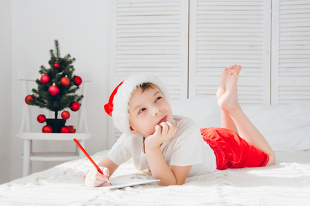 Cute boy in a red hood lies in bed and thinks that he would write the letter to Santa. Christmas concept.