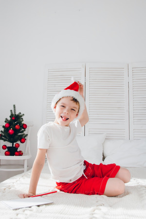 Cute boy in a red cap sits on the bed and builds funny faces. Christmas concept.