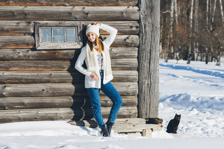 black sweater: Young beautiful girl in hat and mittens in winter, posing near an old log house. Christmas concept. Toning.