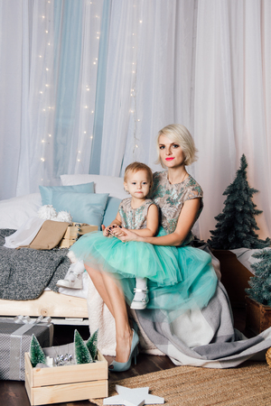 Beautiful young mother and little daughter in puffy skirts made of tulle posing in the new year interior. Christmas concept. Toning.