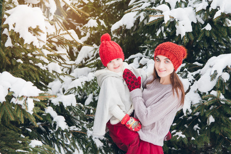 Young beautiful woman and her little daughter have fun in the winter forest with fir trees. Toning. Concept of a family holiday.