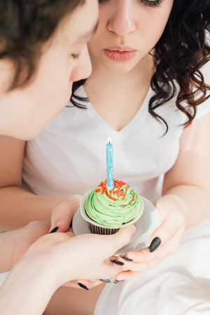 Couple in love celebrates the holiday in bed over a sweet Breakfast. Blowing out candles on cupcakes. The concept of love and romance. Toning.