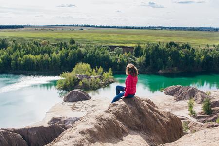 Abandoned sand quarry to the blue lake. Konduki, Tula region, Russia. The girl looks into the distance. Toning.