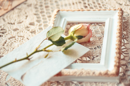 Delicate composition of roses and photo frames decorated in rustic style. Selective focus. Vintage toning.