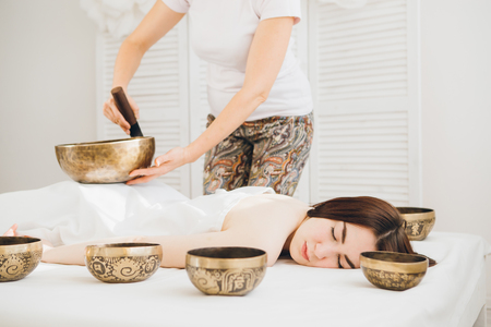 Young beautiful girl doing massage therapy singing bowls in the Spa. The concept of relaxation and alternative medicine. Toning. 스톡 콘텐츠