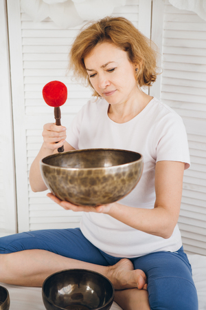 Massage therapist plays on singing bowls for a vibrational massage in the Spa. The concept of relaxation and alternative medicine. Toning.