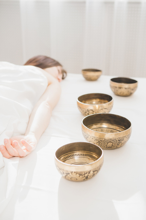Young beautiful girl doing massage therapy singing bowls in the Spa. The concept of relaxation and alternative medicine. Toning. Foto de archivo