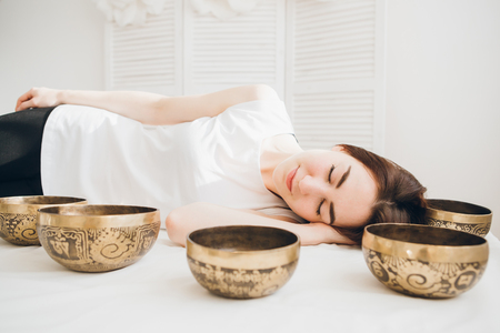 Young beautiful girl doing massage therapy singing bowls in the Spa. The concept of relaxation and alternative medicine. Toning. Stockfoto