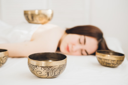 Young beautiful girl doing massage therapy singing bowls in the Spa. The concept of relaxation and alternative medicine. Toning.