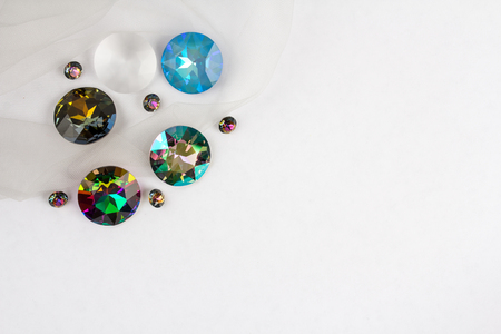 Gemstones crystals for jewelry scattered on white background