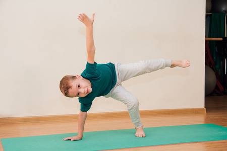Cute little boy is learning to do yoga in the gym. The concept of sport and healthy lifestyle.