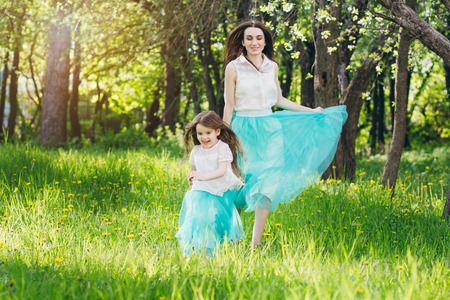 Young mother and a little daughter walk in the spring blooming Apple orchard. Mom plays running after the girl. Toning. Banque d'images