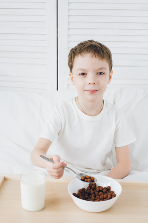 Cute boy eating Breakfast chocolate balls sitting in bed with white linens