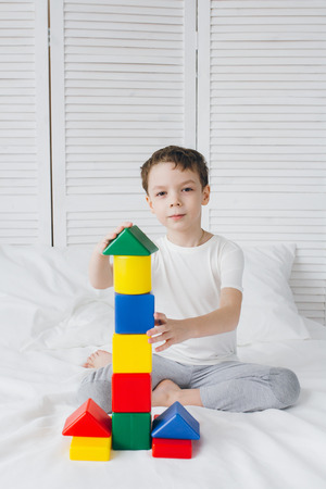 Cute boy plays and builds a tower of colorful plastic cubes sitting on a bed with white linens. Selective focus.