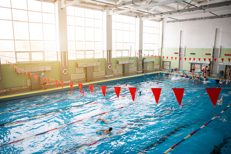 Red flags hanging in the pool at the competition. The concept of sport and health.