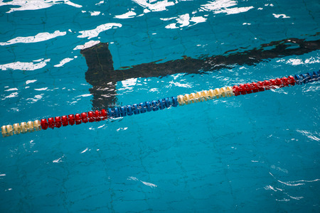 Plastic multi-colored dividers tracks in the pool at the competition. The concept of sport and health.