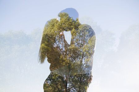 Young loving couple kissing against the sky. Double exposure.Toning.