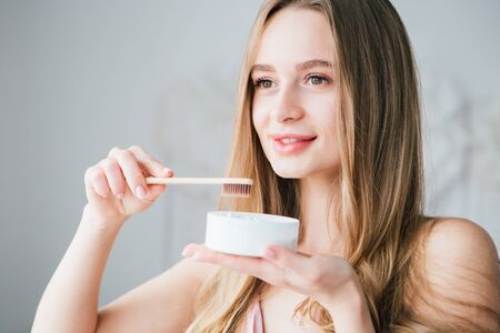 Junges schönes Mädchen, das eine nützliche Bambuszahnbürste und ein Glas Zahnpulver hält. Das Konzept eines gesunden Lebensstils, Umweltfreundlichkeit und Zero Waste. Tonisieren.