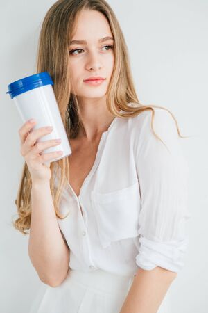Young beautiful girl holding a useful reusable glass for comparison. The concept of sustainability and zero waste. Toning.
