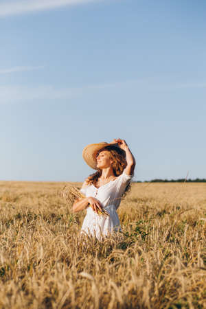 Young beautiful girl with long curly hair poses in a wheat field in the summer at sunset. The girl in the hat. Toning. Imagens