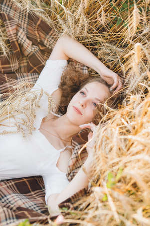 Young beautiful girl with long curly hair poses in a wheat field in the summer at sunset. The girl is lying on a blanket in the wheat. Toning.