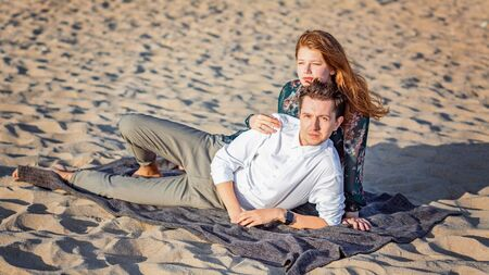 Young couple have a rest on sand in clothes on the seashore, the girl looks into the distance