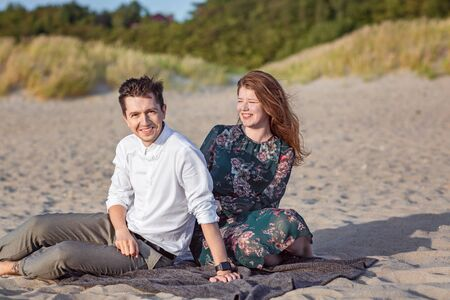 Young couple relax in the sand in clothes on the seashore, laugh and talk