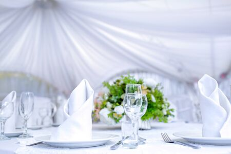 Wedding table with a white tablecloth in a white outdoor tent