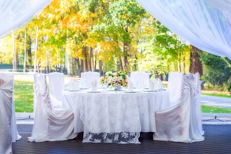 Wedding table with white tablecloth, outdoor setting, view of autumn bright yellow and orange trees