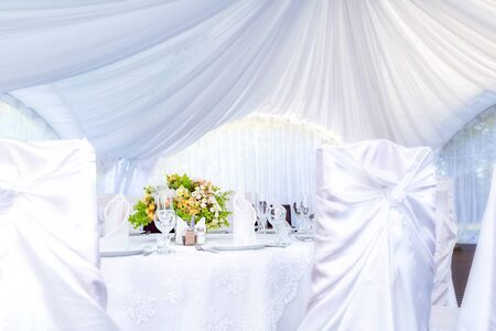 Wedding simple outdoor table setting in a white outdoor tent. Archivio Fotografico