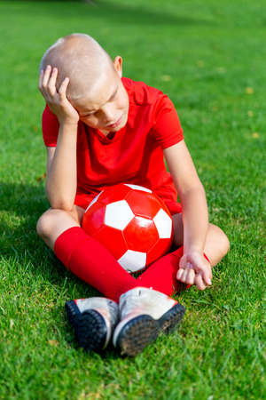 A boy in a red football uniform sits with a ball, leaning his head on his hand, sad