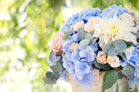 Large bouquet of roses, dahlias, hydrangeas, eucalyptus leaves in a clay pot