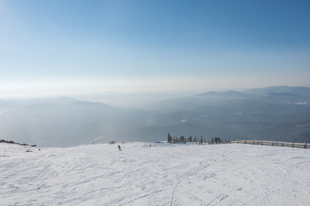 valley below: Top view of the ski slopes, the mountains and the valley below on a sunny day.