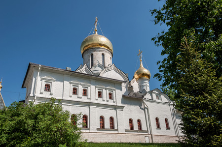 peal: White orthodox church with gold domes inside the monastery on a background of blue sky