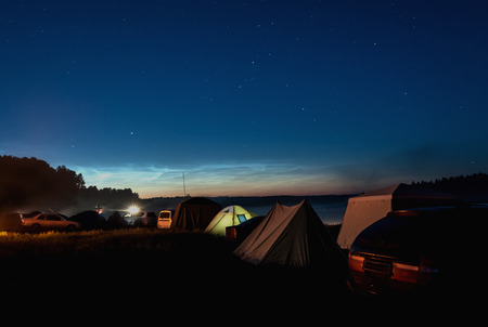 Night view of the tourist camp with tents and cars on the shore of lake on a background of the starry sky with silver clouds photo